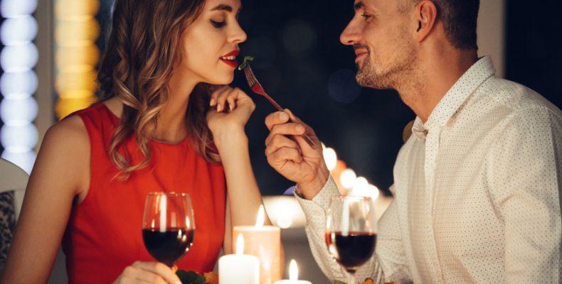 mężczyzna karmi piękną kobietę przy romantycznej kolacji w domu