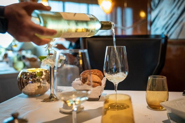 wino wlewane do kieliszka podczas romantycznej kolacji
