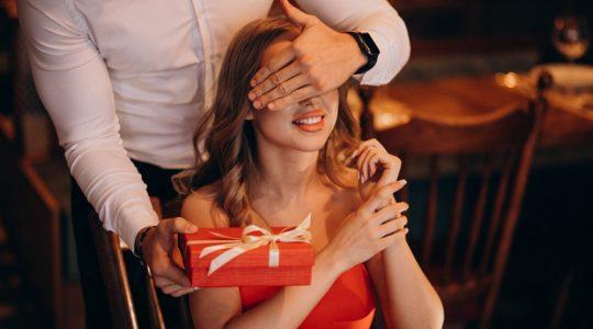 mężczyzna dłonią zasłania uśmiechniętej kobiecie oczy i wręcza czerwony prezent