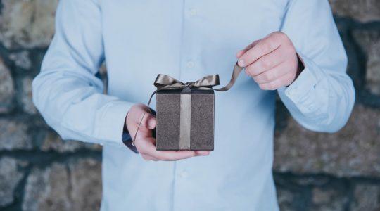 mężczyzna rozpakowuje prezent