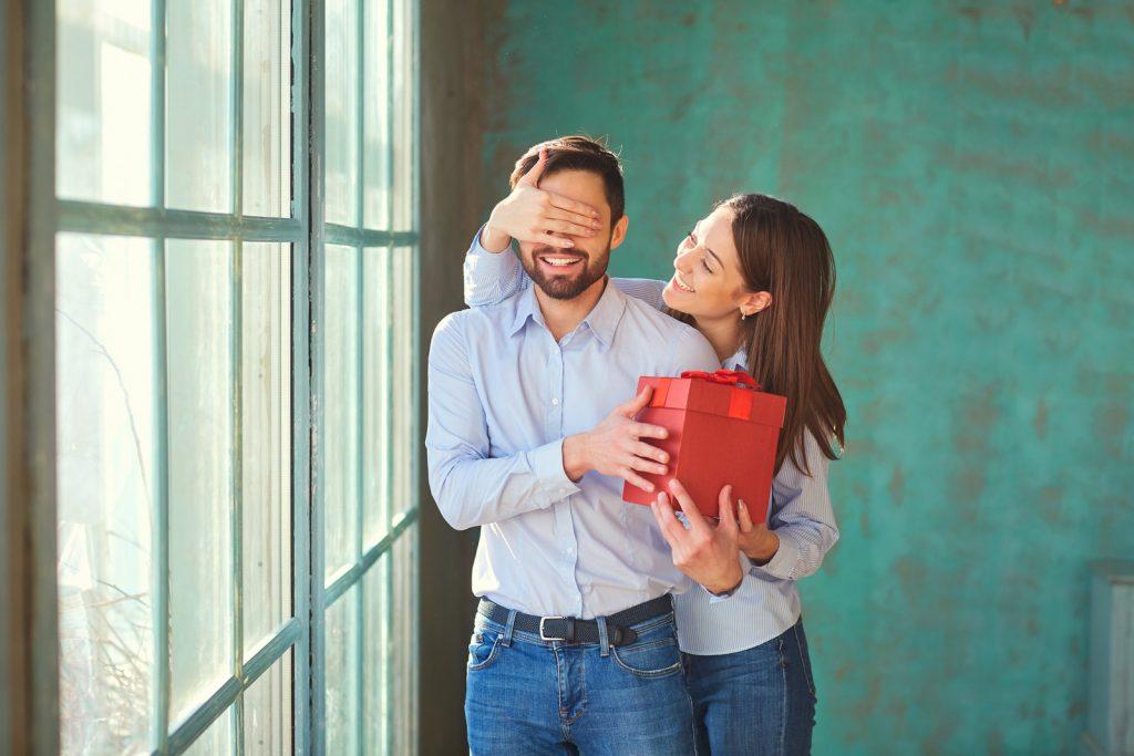 kobieta zasłania oczy mężczyźnie wręczając mu prezent