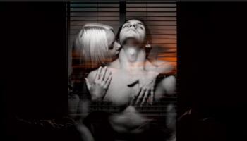 kobieta zmysłowo całuje umięśnionego mężczyznę w szyję