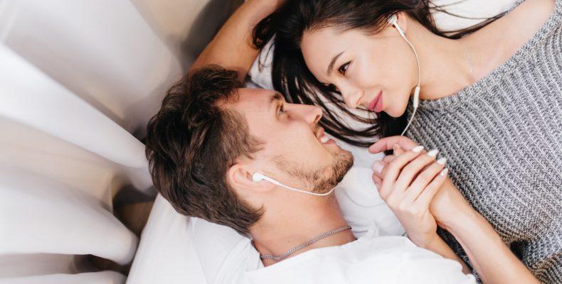 mężczyzna i kobieta leżą w łóżku z słuchawkami w uszach trzymając się za ręce