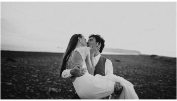 para młoda na polanie, mężczyzna niesie kobietę, czarno-białe zdjęcie