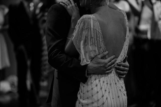 Para młoda, panna młoda objęta przez mężczyznę, czarno-białe zdjęcie.