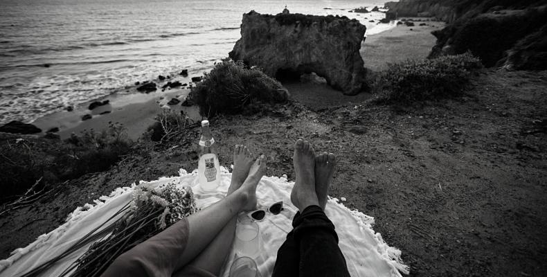 para odpoczywająca na kocu na plaży, widok na klif nad morzem