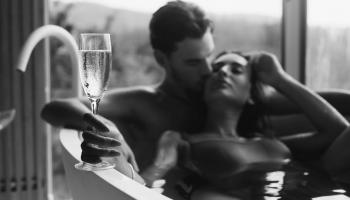 kobieta i mężczyzna w wannie w zmysłowej pozie z lampką szampana