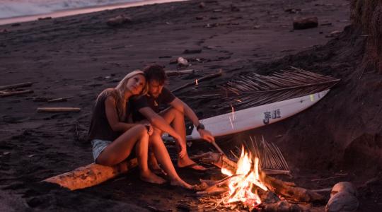 para wtulona w siebie siedzi przy ognisku na plaży