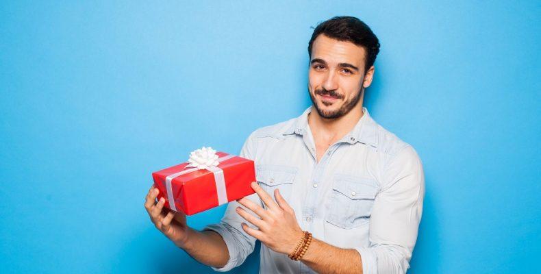 mężczyzna z prezentem koloru czerwonego na niebieskim tle